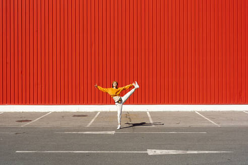Young woman dancing in front of a red wall - ERRF02827