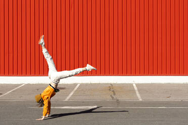 Young woman doing a handstand in front of a red wall - ERRF02830