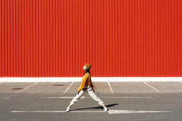 Young woman dancing in front of a red wall - ERRF02833