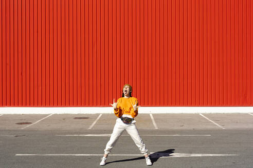 Young woman screaming in front of a red wall - ERRF02836