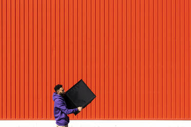 Young man carrying a box in front of a red wall - ERRF02839