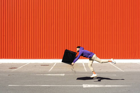 Young man carrying a box in front of a red wall - ERRF02845