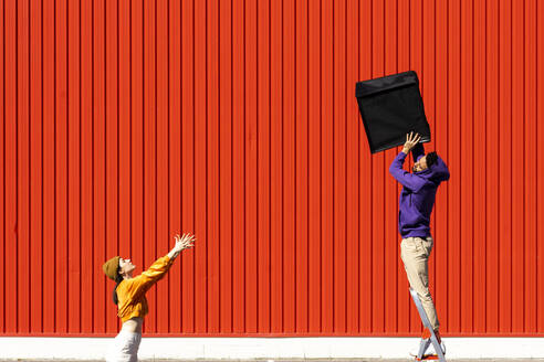 Young man and woman performing with a box in front of a red wall - ERRF02851