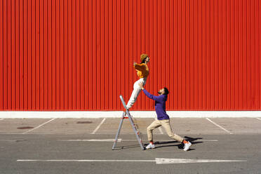 Young man and woman performing with a ladder in front of a red wall - ERRF02857