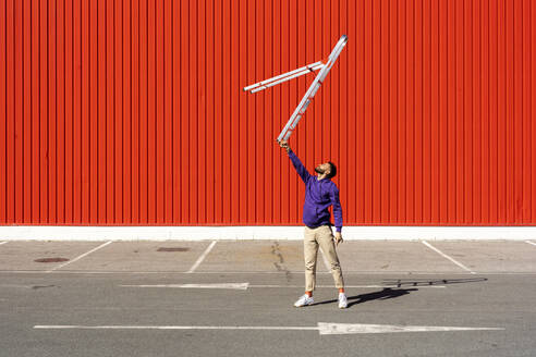 Young man balancing a ladder in front of a red wall - ERRF02860