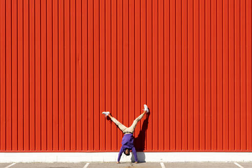 Young man doing a handstand at a red wall - ERRF02863