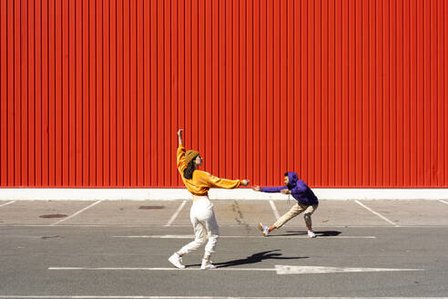 Young man and woman performing in front of a red wall - ERRF02866
