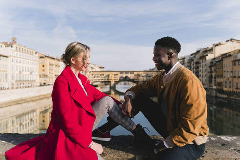 Smiling young couple sitting on a bridge in the city of Florence, Italy - FMOF00887