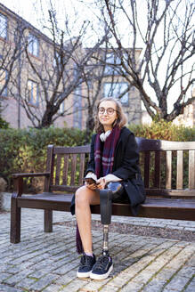 Portrait of confident young woman with leg prosthesis sitting on a bench in the city - FBAF01279