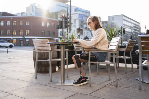 Young woman with leg prosthesis sitting in a sidewalk cafe in the city using laptop - FBAF01282