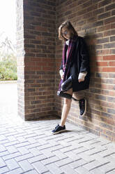 Young woman with leg prosthesis standing at a brick wall - FBAF01288