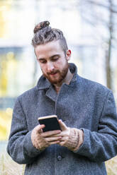 Young man using cell phone in the city - FBAF01306
