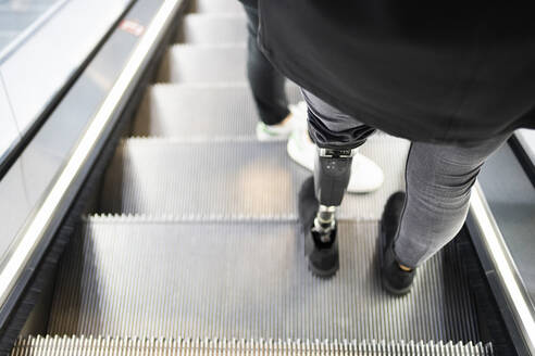Close-up of woman with leg prosthesis standing on escalator - FBAF01312