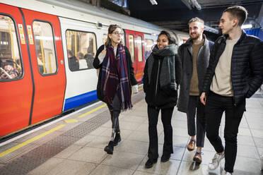 Friends walking at subway station platfom - FBAF01324