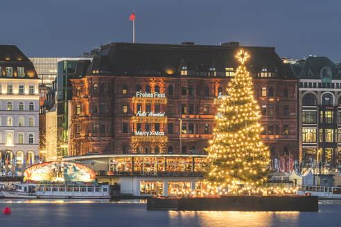 Germany, Hamburg, IlluminatedAlstertannetree at dusk withJungfernstiegpromenade in background - KEBF01486