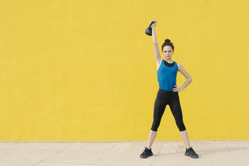 Young woman exercising with dumbbell in front of a yellow wall - JCZF00023