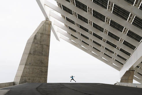 Young woman jogging at a modern building - JCZF00029