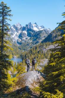 Hikers enjoying view on rock, Alpine Lakes Wilderness, Washington, USA - ISF23881