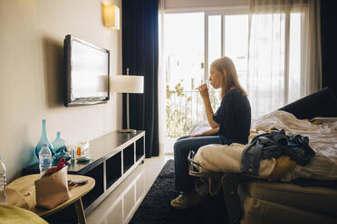 Side view of girl watching television while sitting on bed in hotel room - MASF16780