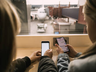 Rear view of siblings using smart phones while sitting at airport - MASF16792