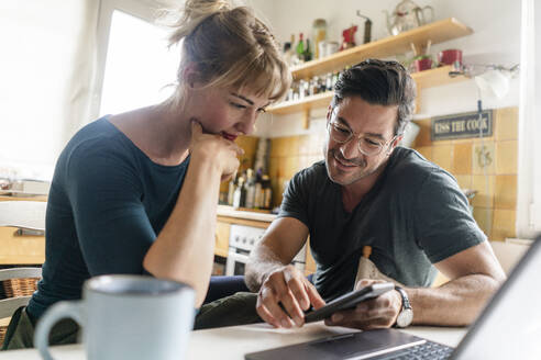 Couple sitting at table in kitchen using smartphone - KNSF07663
