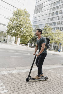 Casual man riding e-scooter in the city - KNSF07675