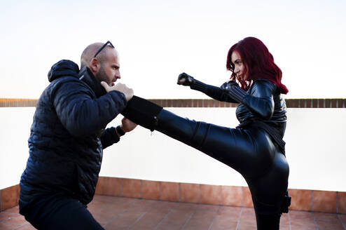 Redheaded woman wearing black leather catsuit fighting against man on rooftop - CJMF00269