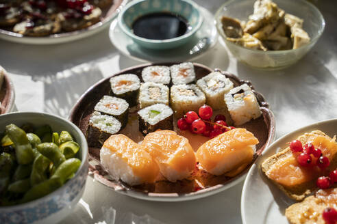 Spain, Plate of ready-to-eat sushi on set dining table - AFVF05461