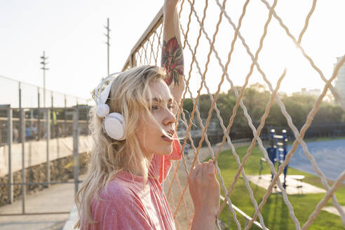 Young woman listening to music at a wire mesh fence - AFVF05487