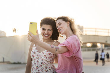 Happy friends taking a selfie outdoors at sunset - AFVF05496