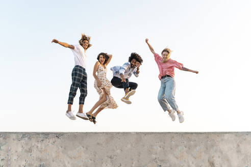 Carefree friends jumping on a concrete wall - AFVF05499