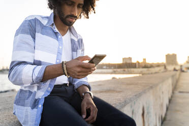 Young man sitting on quay wall at sunset using smartphone - AFVF05505