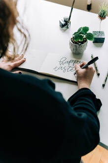Stock photo of a lettering artist at work with her sketch book. - CAVF76018