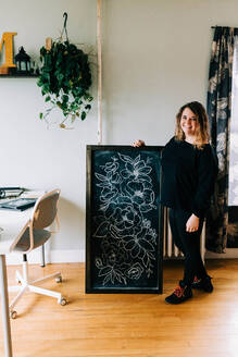 Stock photo of an artist posing with her work. - CAVF76027