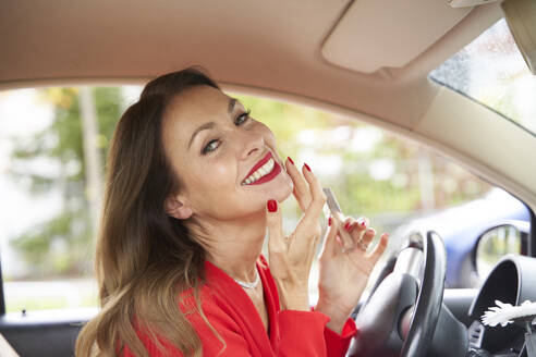 Portrait of happy mature woman with red lips and nails in car - PNEF02464