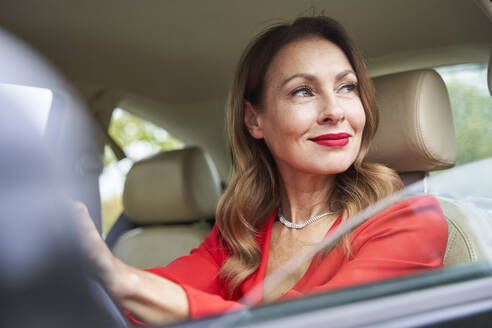 Portrait of smiling mature woman looking out of car window - PNEF02473