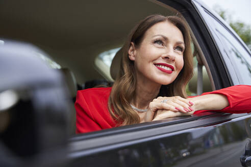 Portrait of smiling mature woman looking out of car window - PNEF02476