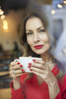 Portrait of mature woman with cup of coffee behind windowpane - PNEF02479