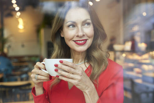 Portrait of smiling mature woman with cup of coffee behind windowpane - PNEF02482