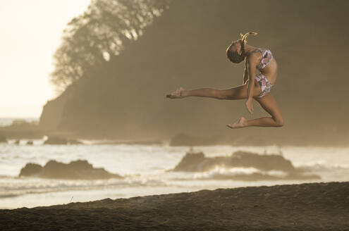 Teenage girl practicing gymnastic at seafront, Jaco Beach, Costa Rica - AMUF00008