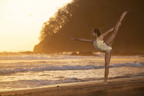Teenage girl practicing gymnastic at seafront by sunset, Jaco Beach, Costa Rica - AMUF00011