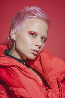 Portrait of young woman with short pink hair wearing red jacket in front of red background - VPIF02120