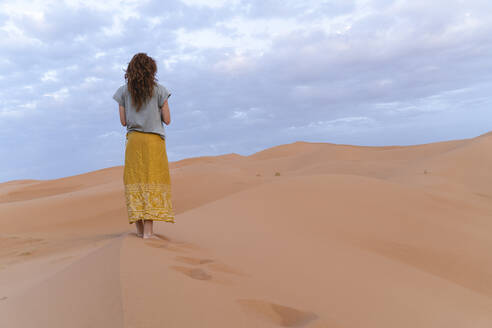 Young woman standing on sand dune in Sahara Desert, Merzouga, Morocco - AFVF05532
