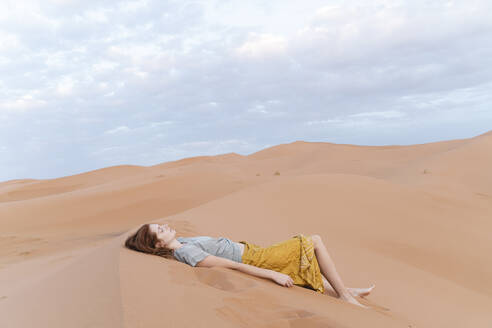 Young woman lying in sand dune in Sahara Desert, Merzouga, Morocco - AFVF05535