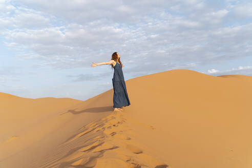 Young woman standing on sand dune in Sahara Desert with outstretched arms, Merzouga, Morocco - AFVF05550