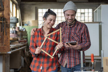 Portrait of happy craftswoman and craftsman holding tablet and yardstick in their workshop - MOEF02836