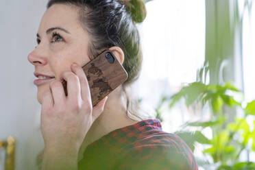 Portait of smiling woman using wooden cell phone - MOEF02845