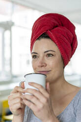 Portrait of woman with head wrapped in a towel drinking a coffee - MOEF02851