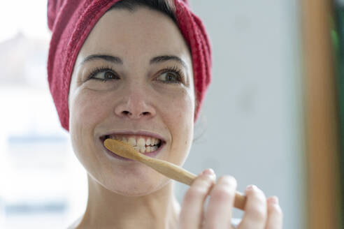 Portrait of woman with head wrapped in a towel brushing heer teeth with wooden toothbrush - MOEF02857