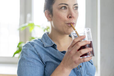 Portrait of woman having a drink using wooden straw - MOEF02860
